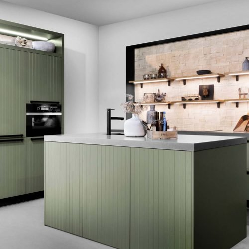 Green contemporary kitchen with black taps