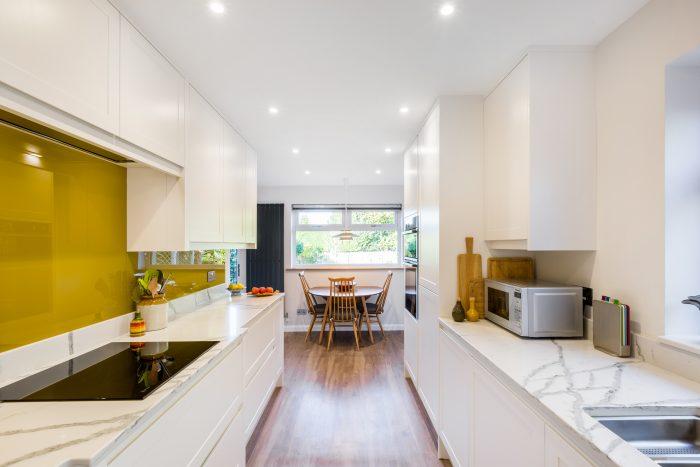Contemporary kitchen with mustard splashback and quartz worktop