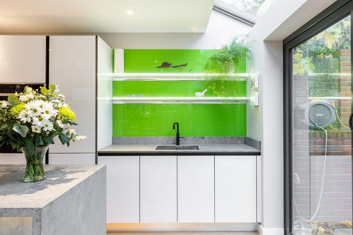 modern white gloss handleless ktichen with green glass splashback